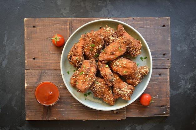 Gebakken kippenvleugels met sesamzaadjes. ketchup en chilisaus. vrije ruimte voor tekst. bovenaanzicht. heerlijke gebakken kippenvleugels.