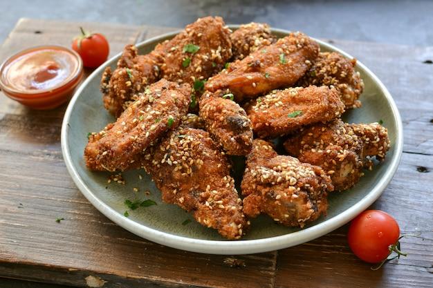 Gebakken kippenvleugels met sesamzaadjes. ketchup en chilisaus. vrije ruimte voor tekst. houten tafel. heerlijke gebakken kippenvleugels. detailopname