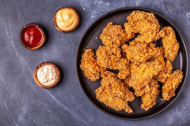Gebakken kippenvleugels met verschillende sauzen, bovenaanzicht.