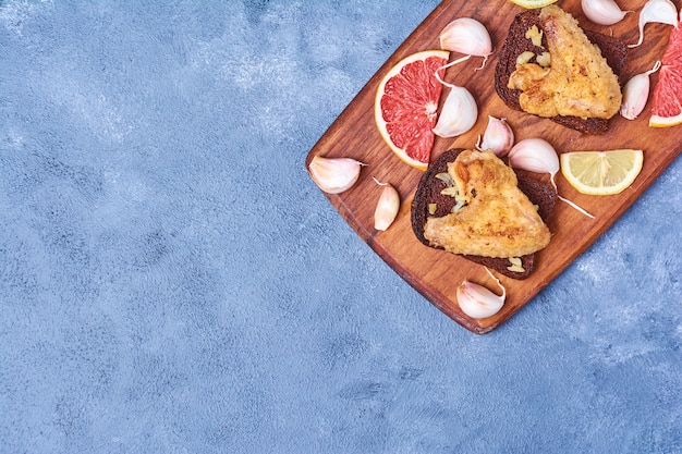 Gebakken kippenvleugels op een houten bord op blauw