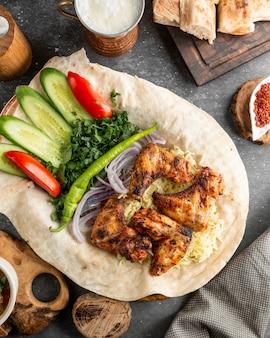 Gebakken kippenvleugeltjes geserveerd met verse salade en uien