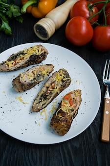 Gebakken kiprolletjes met kaas, greens geserveerd op een witte plaat. verse groenten.