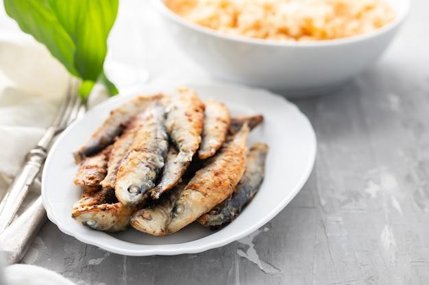 Gebakken kleine sardines met tomatenrijst op witte schotel op keramische achtergrond