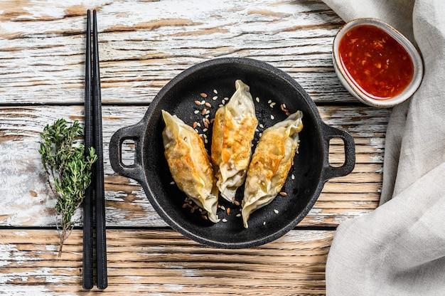 Gebakken knoedels in een pan, chinees eten koken. witte ruimte. bovenaanzicht