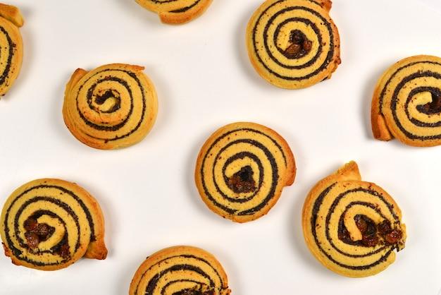 Gebakken koekjes met rozijnen en maanzaad geïsoleerd op een witte achtergrond.