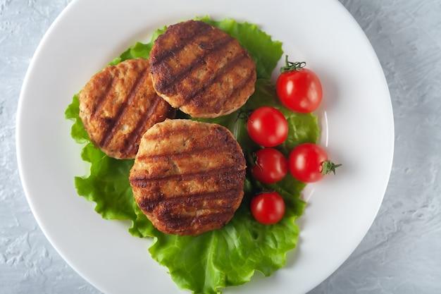 Gebakken kotelet met salade en tomaten in een witte plaat op een grijze achtergrond