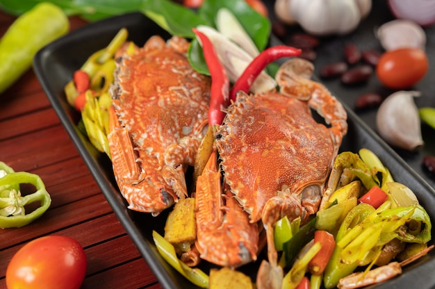 Gebakken krab met kerriepoeder in een bord met paprika en tomaten.