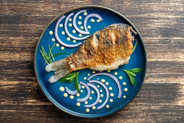 Gebakken kroeskarper met ui en saus dot schilderij op een plaat op een houten tafel. bovenaanzicht, close-up
