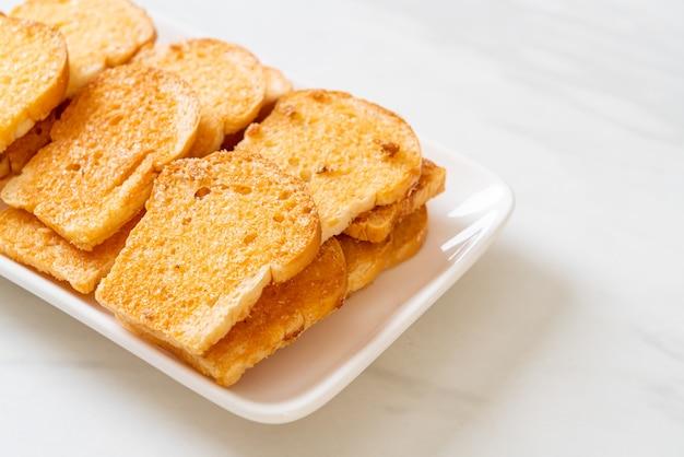Gebakken krokant brood met boter en suiker op bord