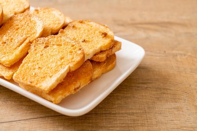 Gebakken krokant brood met boter en suiker op plaat