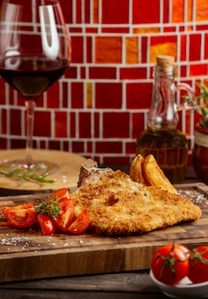 Gebakken krokante kip geserveerd met tomaat en gebakken aardappelen op een houten bord