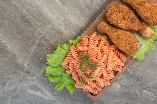 Gebakken krokante kipnuggets met heerlijke macaroni op houten bord.