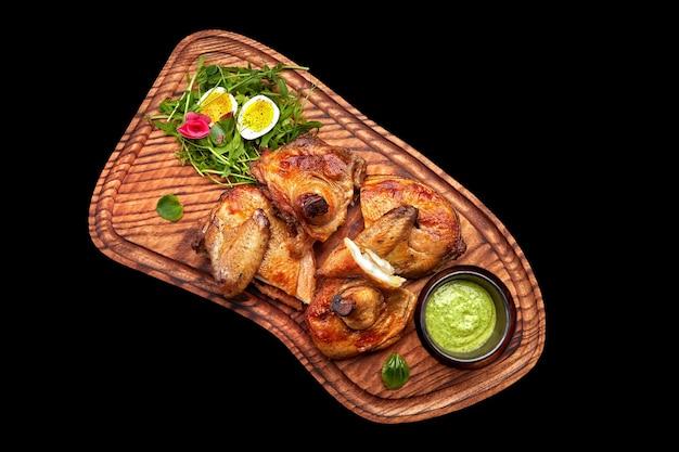 Gebakken kuiken met kruiden en saus op een houten bord op een zwarte achtergrond isolate