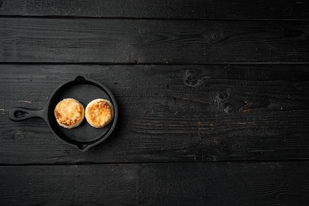 Gebakken kwarkpannenkoekjes op gietijzeren koekenpan op gietijzeren koekenpan, bovenaanzicht plat, op oude donkere houten tafel