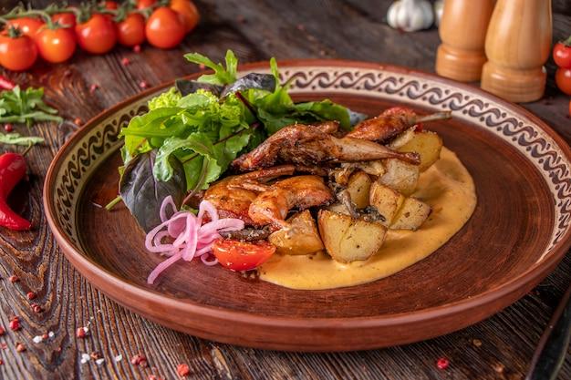 Gebakken kwartels met aardappelen geserveerd met saffraansaus en groene salade, een restaurantgerecht, close-up, horizontale oriëntatie