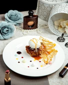 Gebakken lamsvlees gegarneerd met vanille-ijs geplaatst naast lippenstift en parfum