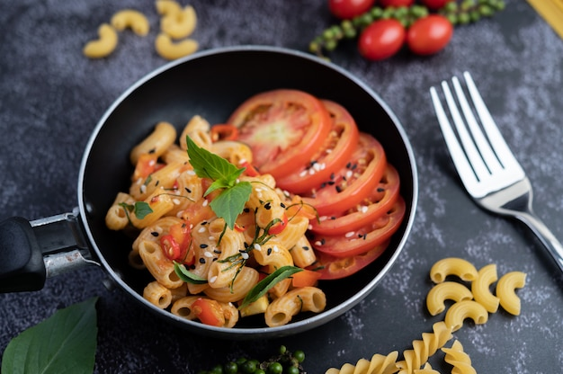 Gebakken macaroni en worst in een koekenpan.