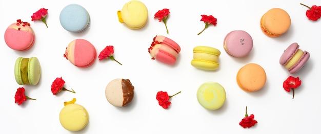 Gebakken macarons met verschillende smaken en rosebuds op een witte achtergrond, bovenaanzicht
