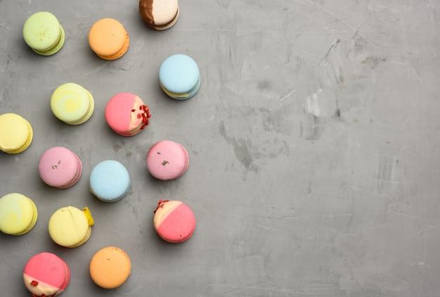 Gebakken macarons met verschillende smaken op een grijze cementachtergrond, bovenaanzicht, kopieerruimte