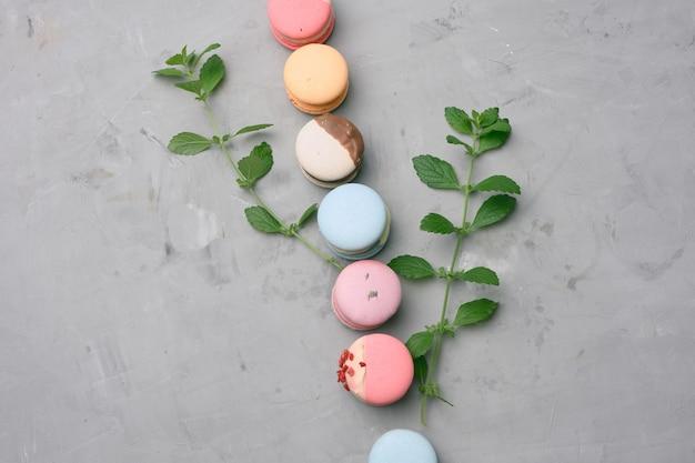 Gebakken macarons met verschillende smaken op een grijze cementachtergrond, bovenaanzicht