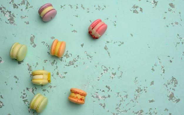 Gebakken macarons met verschillende smaken op een groene achtergrond, bovenaanzicht