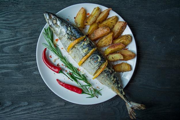 Gebakken makreel met citroen en aardappelen in de schil op een witte plaat.