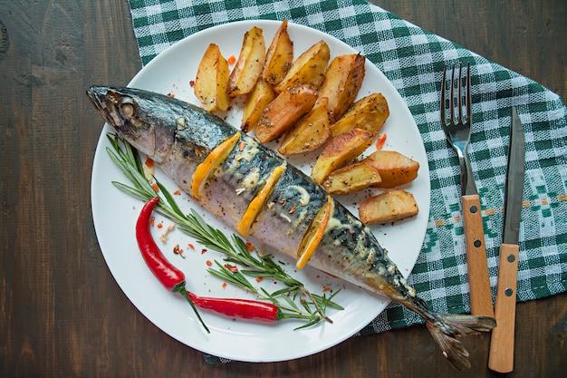 Gebakken makreel met citroen en gebakken aardappelen. verse groenten. bovenaanzicht. plaats voor tekst. donkere houten achtergrond. ruimte voor tekst. voedsel achtergrond. de balans van gezond eten.