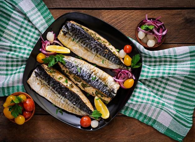 Gebakken makreel met kruiden en gegarneerd met citroen en groenten in het zuur. bovenaanzicht