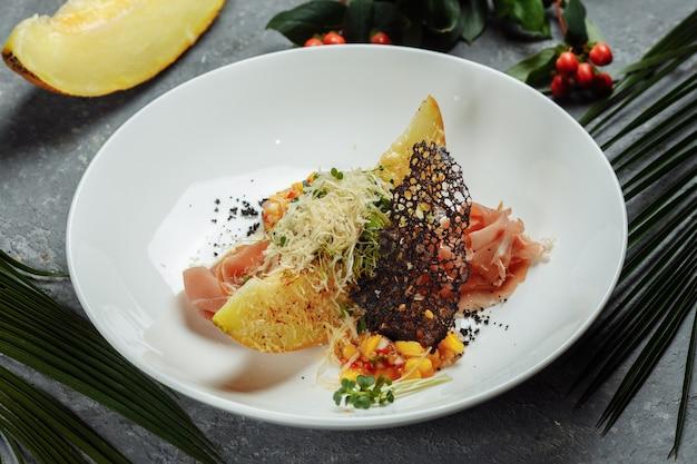 Gebakken meloen met parmezaanse kaas en jamon op een wit bord
