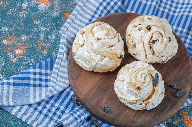 Gebakken meringue cookie met zwarte rozijnen op een houten bord.