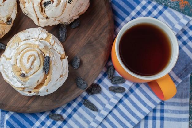 Gebakken meringuekoekje met zwarte rozijnen en een kopje thee.