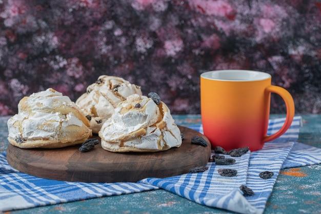 Gebakken meringuekoekje met zwarte rozijnen en witte chocolade bovenop geserveerd met een kopje drank.