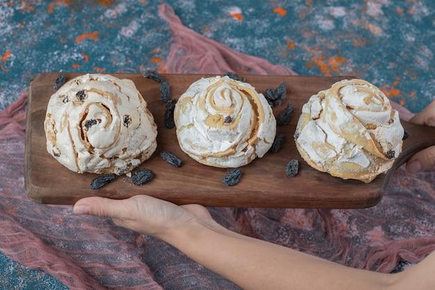 Gebakken meringuekoekje met zwarte rozijnen op een houten bord.