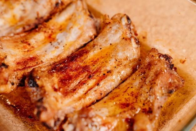 Gebakken met kruiden varkensribbetjes in een glazen bakplaat op een houten ondergrond. thuis gekookt vlees.