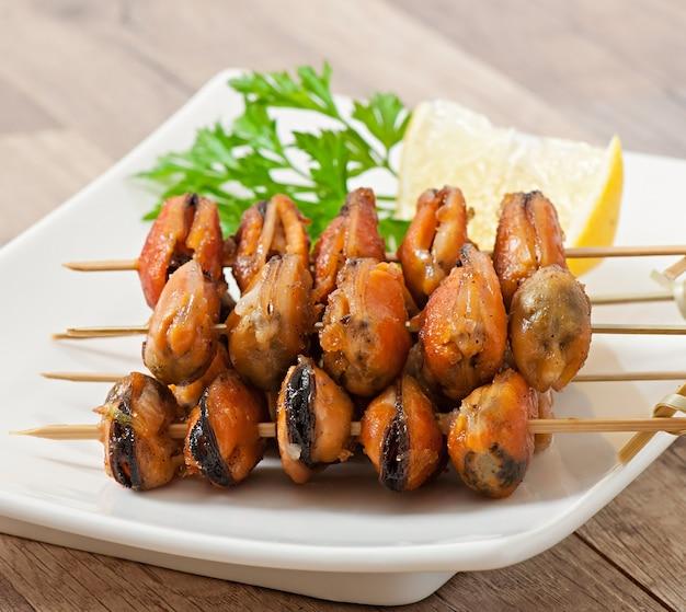 Gebakken mosselen met uien op spiesjes c garnituur van sperziebonen en paprika