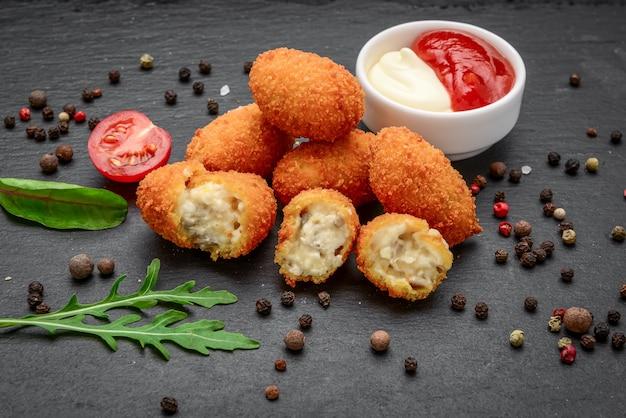 Gebakken mozzarella, cheddar cheese bites, balletjes met ketchup op rustieke stenen plank
