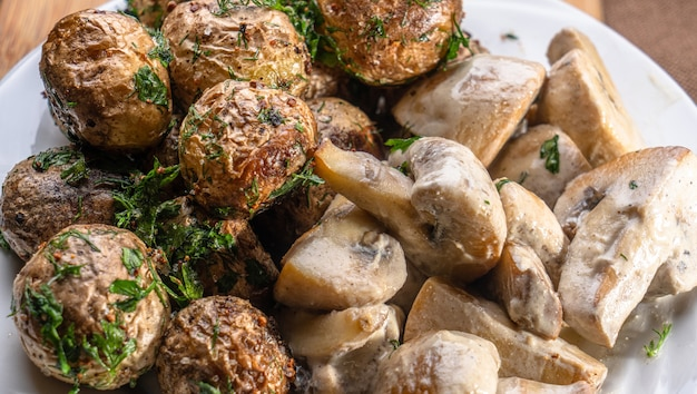 Gebakken nieuwe aardappelen met een korst met champignons in een close-up van een romige saus op een houten bord. smakelijk huisgemaakt of restauranteten