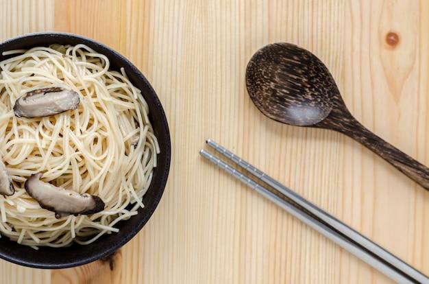 Gebakken noedels in zwarte kom op houten tafel, thaise straatvoedsel