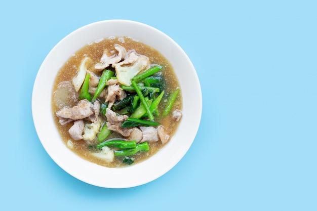 Gebakken noedels met varkensvlees en chinese broccol, bloemkool in witte schotel op blauwe achtergrond.