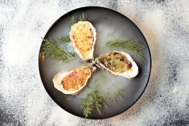 Gebakken oesters met kaas in een zwarte plaat