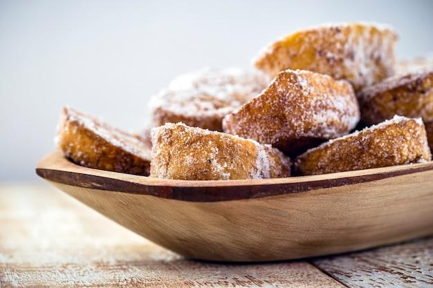 Gebakken of gebakken brood met kaneel en suiker in een antieke koperen schuimspaan