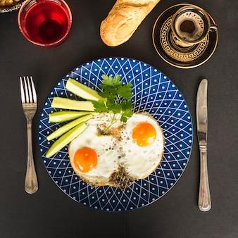 Gebakken omelet met plakjes komkommer en koriander op blauwe plaat