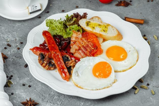 Gebakken ontbijt met spek met worstjes en gebakken bonen