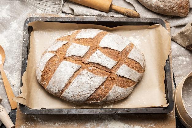 Gebakken ovaal brood van roggemeel in een metalen bakplaat op tafel, bovenaanzicht