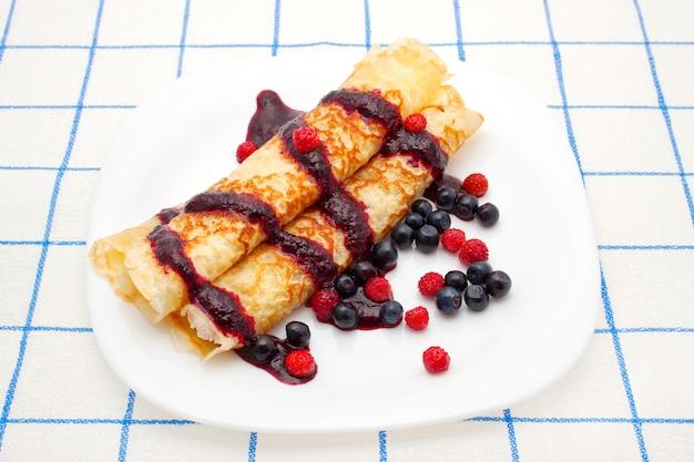 Gebakken pannenkoeken met bessensaus, bosbessen en aardbeien