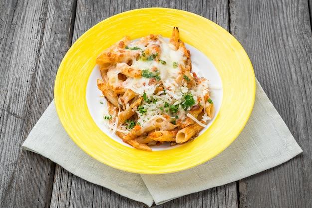 Gebakken pasta met kaas. de braadpan van ricotta van de worstspinazie op houten achtergrond