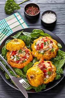 Gebakken pattypan squash gevuld met rijst, gebakken kippenvlees, krokant gebakken bacon, rode paprika en geserveerd met spinazieblaadjes en peterselie op een zwarte plaat met vork en mes