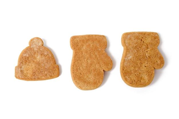 Gebakken peperkoek kerstkoekjes in de vorm van wanten en hoeden geïsoleerd op een witte achtergrond, blanco voor schilderen