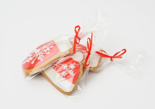 Gebakken peperkoek kerstkoekjes in een polyethyleen zak op een wit oppervlak, close-up