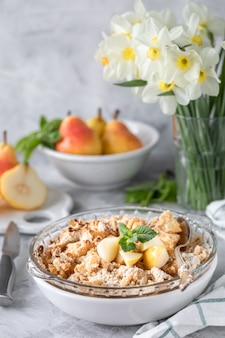 Gebakken peren crumble met peren en honing in een witte schotel op tafel met koperen keukengerei en bloemen